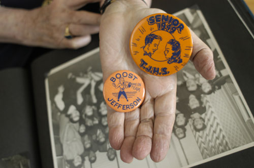 Regina Gelb holds buttons from her high school days.