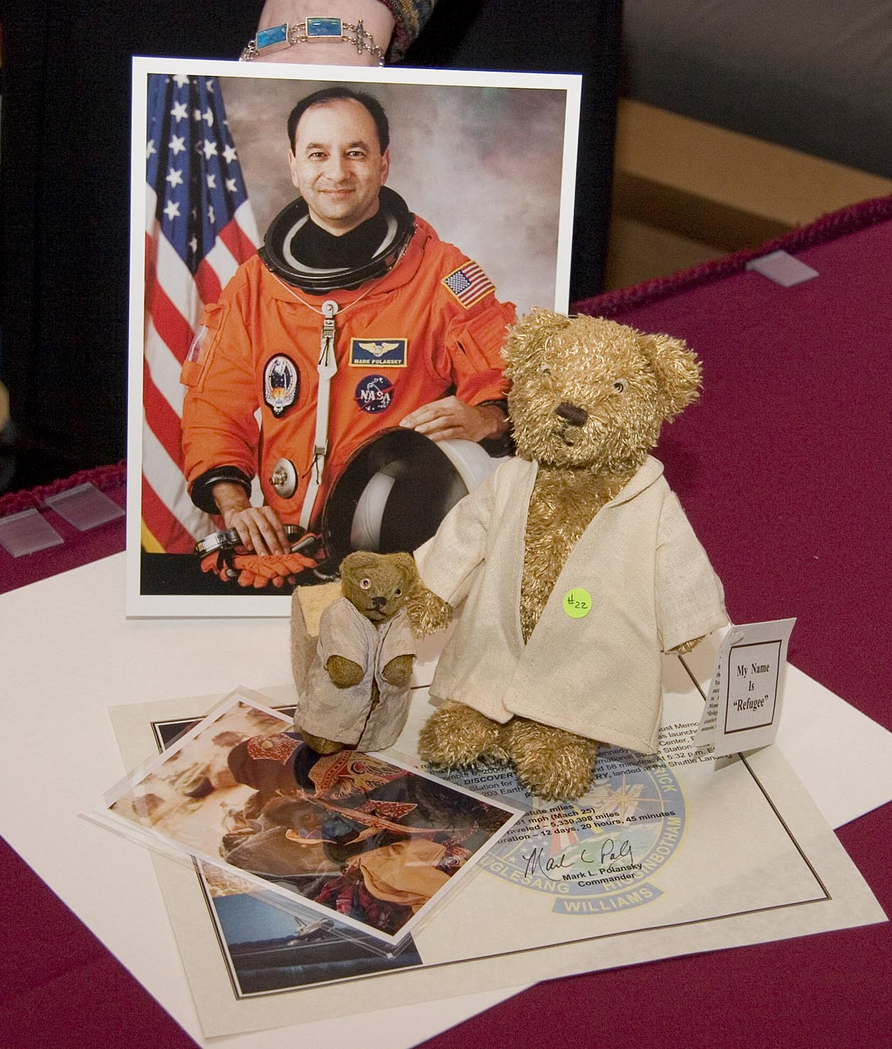 "A replica of ""Refugee"" and a photo of a Darfurian child refugee, items taken by Commander Mark Polansky (pictured) on a December 2006 Space Shuttle mission."