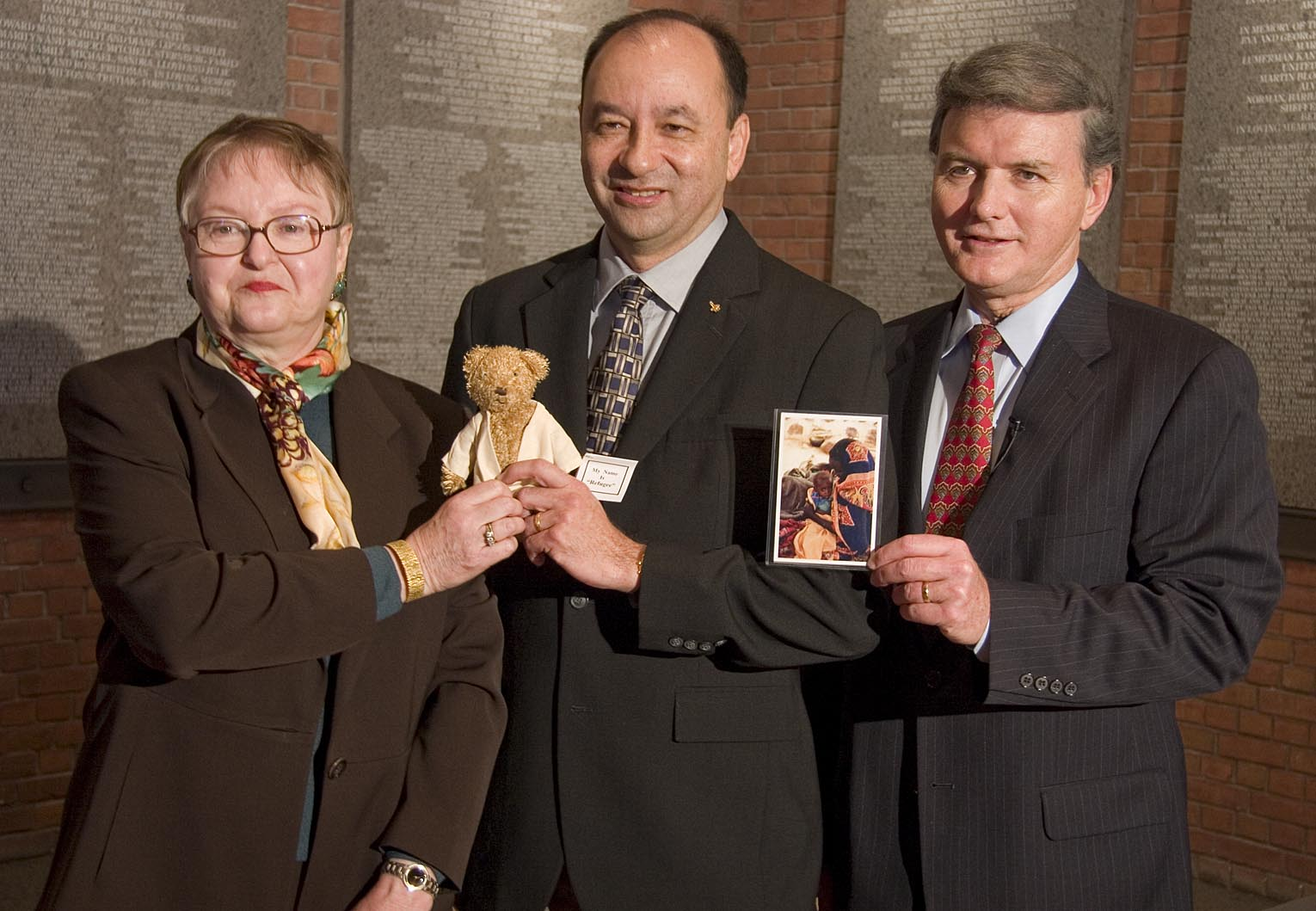 """Dr. Sophie Turner-Zaretsky, Space Shuttle Discovery Commander Mark Polansky , and United States Holocaust Memorial Museum chief of staff Bill Parsons. They  are holding a replica of """"Refugee"""" bear and a photo of a Darfurian child refugee, items taken by Commander Polansky on a December 2006 Space Shuttle mission."""