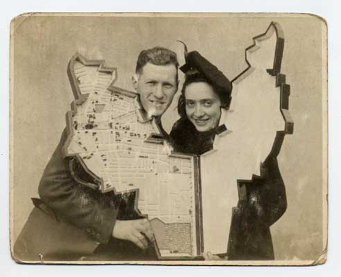 "Leon Jakubowicz and his wife Rachela holding the model of the Lodz ghetto that Leon created. The model recreates, on a small scale, the physical appearance of the ghetto, creating the shape of the model to mimic the exact boundaries, streets, and buildings that had a major impact on daily life in the ghetto. Lodz, Poland, between 1940 and 1944. (Examine the artifact in detail with the ""zoom"" tool below)"