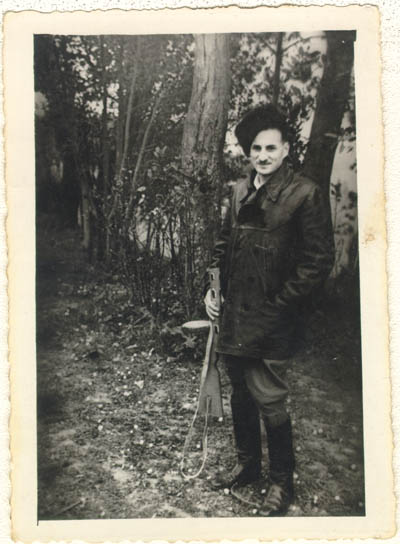 Aron Derman while he was with Polish partisans in 1944. In this photograph, Aron wears a fur hat that he made and boots that he finished himself (he found them in the ghetto, unfinished, and sewed them up). Lisa Nussbaum was also a member of the partisans. Aron recounted that for a short while, Lisa was in charge of 200 women. Photograph taken in 1944, in a partisan base in the Naroch forest.