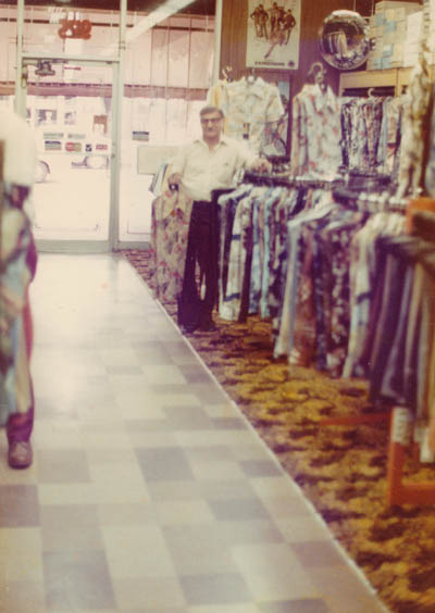 Aron standing in Howard's men's clothing store (named for his eldest son) at 9125 Commercial Avenue in Chicago. He opened the store in 1949 and owned it for 30 years. Chicago, Illinois, early 1970s.