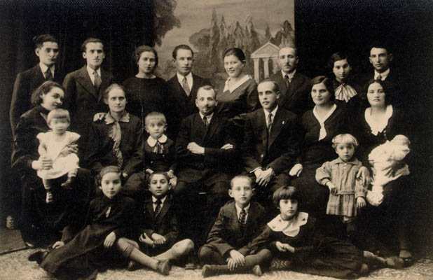 "Portrait of Aron's family on his mother's side, taken when Aron's cousin moved to Israel in 1933-1934. Aron is seated second from left, bottom row. His mother, Miriam, is in the center row, second from right. Aron's father is behind her and to her right. Aron himself was 8 or 9 years old when this picture was taken in either May or June. At the time, Aron recalled, ""I was thinking about going to summer camp."" Slonim, Poland, 1933-1934."