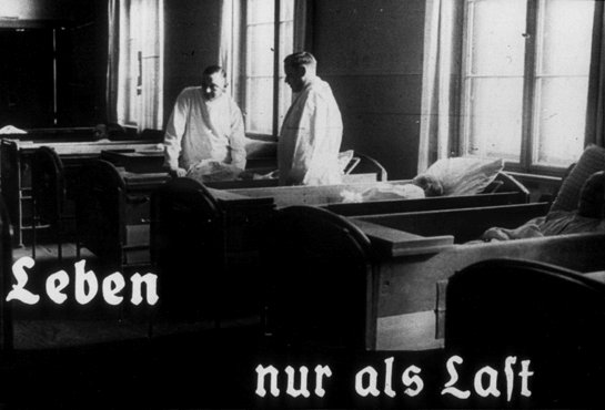 "This photo originates from a film produced by the Reich Propaganda Ministry. It shows two doctors in a ward in an unidentified asylum. The existence of the patients in the ward is described as ""life only as a burden."" Such propaganda images were intended to develop public sympathy for the Euthanasia Program."