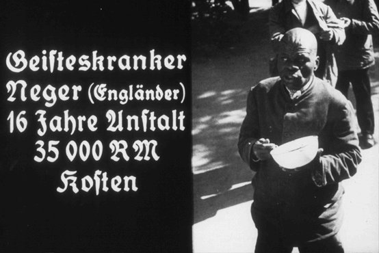 "Slide taken from a Nazi propaganda filmstrip, promoting ""euthanasia,"" prepared for the Hitler Youth. The caption says: ""Mentally ill Negro (English) 16 years in an institution costing 35,000 RM [Reichsmarks]."" Place and date uncertain."