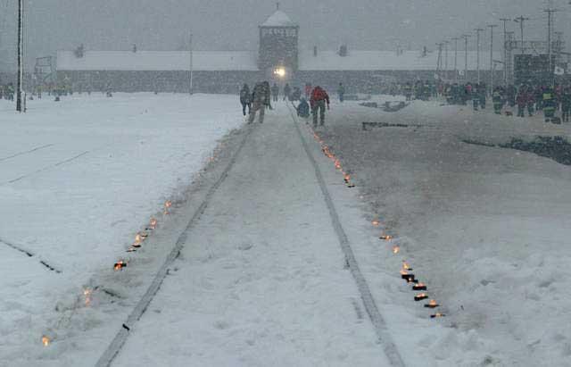 Auschwitz kampının tasfiye edilmesinin 60. yıldönümü kutlamalarında mumlar kampa doğru giden demiryolu raylarını gösteriyor. 27 Ocak 2005, Polonya.