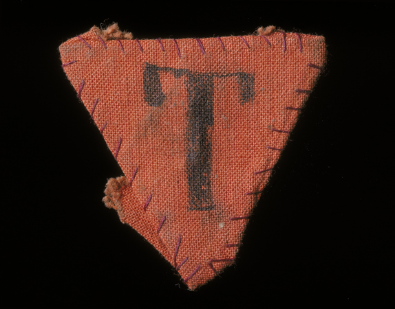 "Red triangle patch worn by Czech political prisoner Karel Bruml in Theresienstadt. The letter ""T"" stands for ""Tscheche"" (Czech in German)."