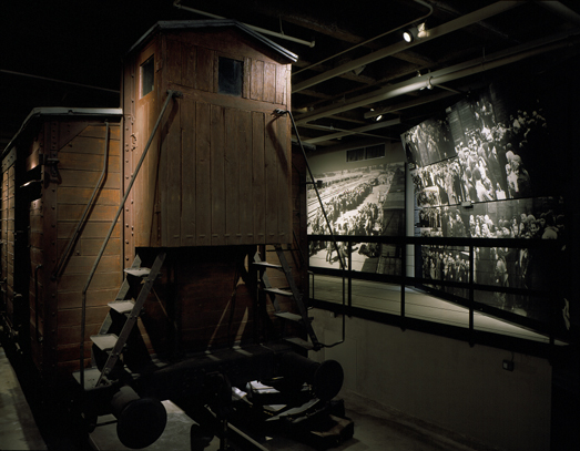 "Front view of the railcar with the ""Selection of Hungarian Jews"" murals in the background on display on the third floor of the Permanent Exhibition at the United States Holocaust Memorial Museum. Washington, DC,  November 3, 1995."