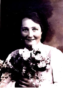 Formal portrait of Frieda Greinegger holding a bouquet of flowers. In 1946, Frieda married Julian Noga, a Polish forced laborer who had been assigned to work on her father's farm in northern Austria. In 1941, the Gestapo had sent both Frieda and Julian to concentration camps as punishment for this forbidden friendship between an Austrian and a Pole. Place and date uncertain.