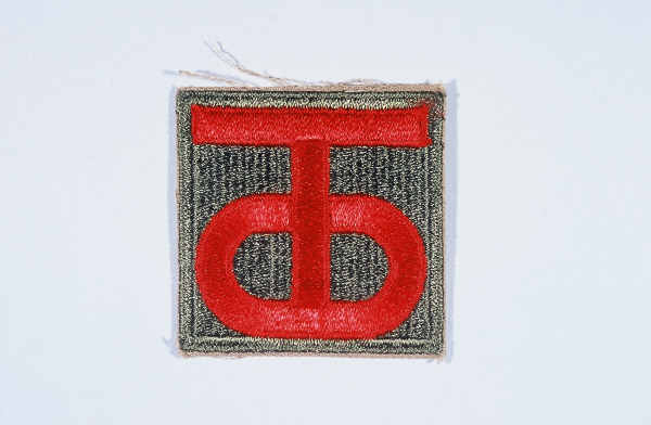 "Insignia of the 90th Infantry Division. Called the ""Tough Ombres,"" the 90th Infantry Division was raised from draftees from the states of Texas and Oklahoma during World War I. The divisional insignia incorporates the letters ""T"" and ""O"" to symbolize both states. These letters later yielded the nickname ""Tough Ombres,"" symbolizing the esprit de corps of the unit. The 90th was also sometimes called the ""Alamo"" division during World War II."