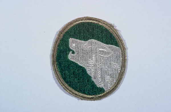 "Insignia of the 104th Infantry Division. The nickname of the 104th Infantry Division, ""Timberwolf,"" originated from the division's insignia, a gray timberwolf. The timberwolf, native to the Pacific Northwest, was chosen as representative of the area where the division was formed in 1942."