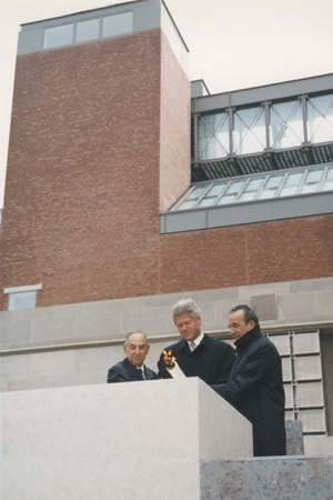 President Bill Clinton (center), Elie Wiesel (right), and Harvey Meyerhoff (left) light the eternal flame outside on the Eisenhower Plaza during the dedication ceremony of the United States Holocaust Memorial Museum. April 22, 1993.