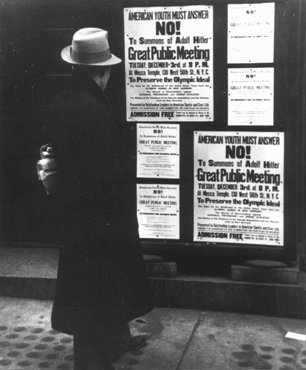 A pedestrian pauses to read a notice announcing an upcoming public meeting, scheduled for Tuesday, December 3, to urge Americans to boycott the 1936 Berlin Olympics. New York, United States, 1935.