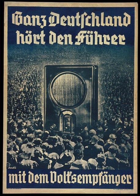 """Poster del 1936: """"La Germania intera ascolta il  Führer alla Radio del Popolo"""". Questo poster mostra una folla di persone radunate attorno a un apparecchio radiofonico le cui dimensioni simboleggiano allo stesso tempo l'attrazione delle masse verso la radio e la vasta audience delle trasmissioni naziste. Bundesarchiv Koblenz (Plak003-022-025)"""