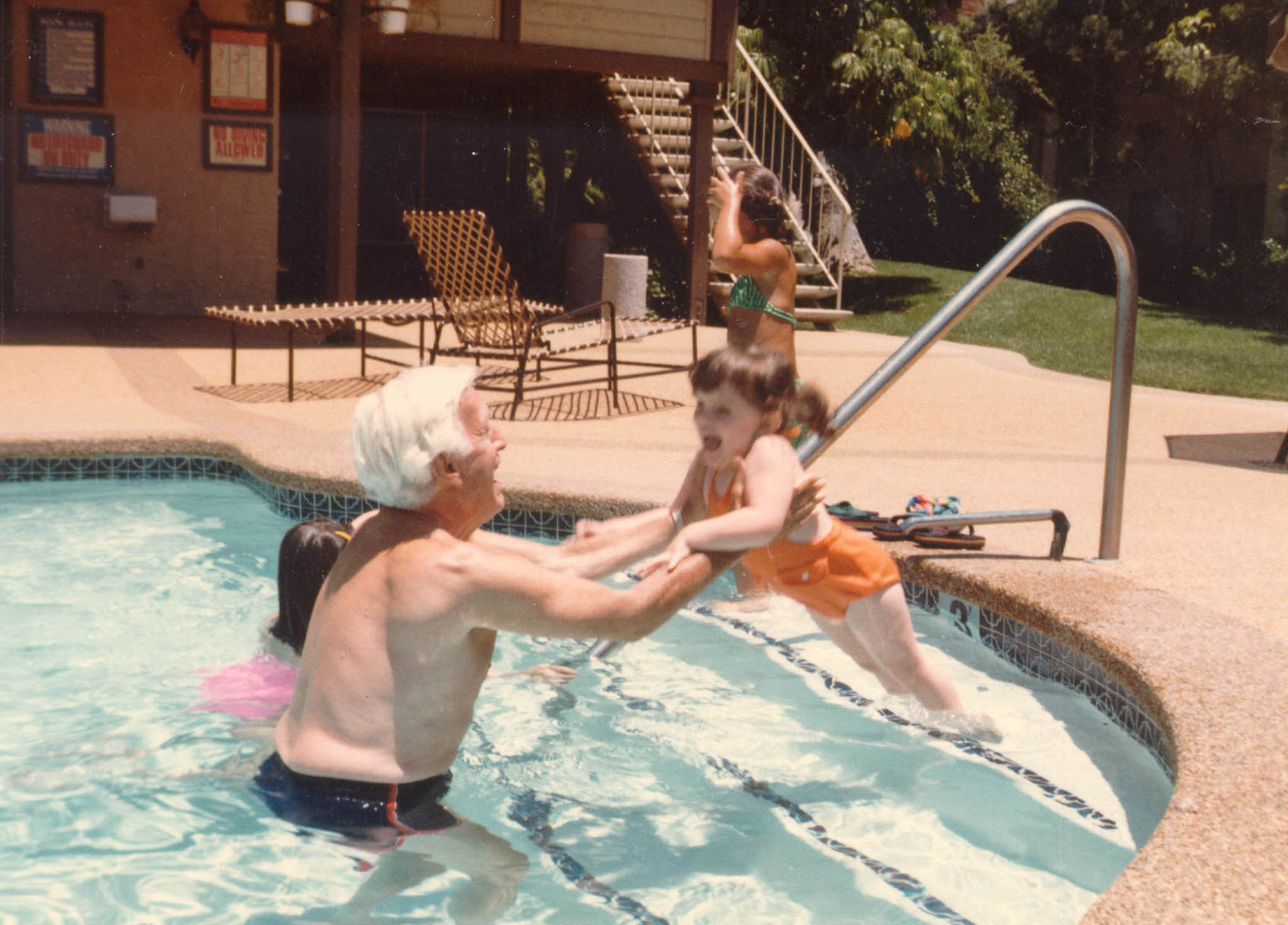 Harry teaching granddaughter Alexis Danielle how to swim, probably in San Diego, California.