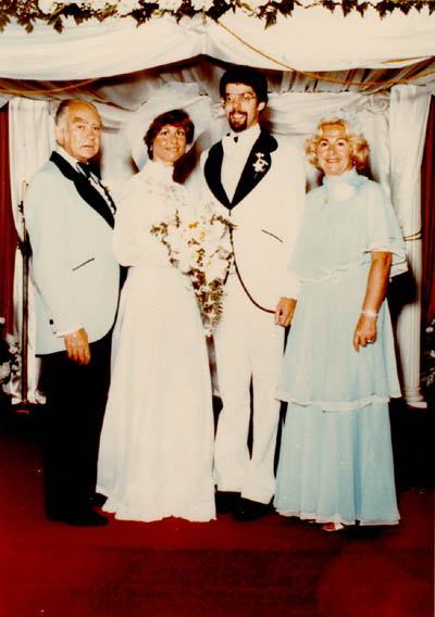 Photograph taken at the marriage of Esther Salsitz and her fiance. Esther's parents, Norman and Amalie, stand at left and right (respectively). June 19, 1977.