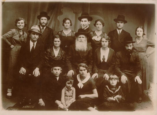 1934 portrait of Norman's family with Norman seated in the front row (at left). In the top row, center, an image of one of Norman's brothers has been pasted into the photograph. This is seen by comparing the size of the brother's face with the others pictured. Pasting in images of family members who could not be present during family portraits was common practice and in some cases the resulting composite images are the only remaining visual records of family groups.