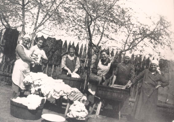 Four of Norman's sisters, the maid, and Norman's mother, Esther, do laundry in the yard of their home. Kolbuszowa, Poland, 1934.