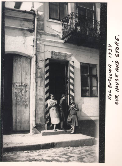 Norman's sisters Malcia, Matla, and Rachel eat bagels in the doorway of their mother's store. The red and white stripes on the door frames indicate that the store carried cigarettes, matches, and sugar, consumer goods regulated by a state monopoly. Kolbuszowa, Poland, 1934.
