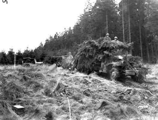 An American anti-aircraft gun, towed by a truck camouflaged with foliage, moves into position in the Hürtgen Forest to provide fire support against ground targets. November 6, 1944. US Army Signal Corps photograph taken by C A Corrado.