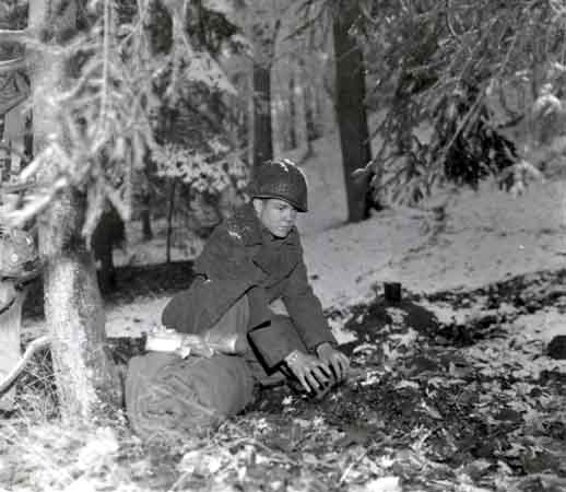 A soldier prepares to bed down for the night in a Belgian forest during the Battle of the Bulge. December 21, 1944. US Army Signal Corps photograph taken by J Malan Heslop.