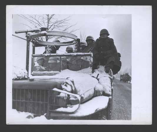 GIs move up to the front in open trucks in subzero weather to stop the German advance. December 22, 1944. US Army Signal Corps photograph taken by  J Malan Heslop.