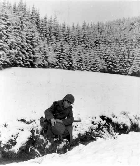 An American GI draws water from a stream with his steel helmet. December 22, 1944. US Army Signal Corps photograph taken by  J Malan Heslop.