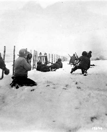 John Perry, a movie photographer with Unit 129, films GIs of the 290th Infantry Regiment, 75th Infantry Division, and 4th Cavalry Group ferreting out German snipers near Beffe, Belgium, in early January 1945. Twelve Germans were killed. The scene was photographed by Carmen Corrado of the 129th. January 7, 1945. US Army Signal Corps photograph taken by C.A. Corrado.