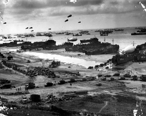 The Normandy beach as it appeared after D-Day. Landing craft on the beach unload troops and supplies transferred from transports offshore. Barrage balloons hover overhead to deter German aircraft. Undated.
