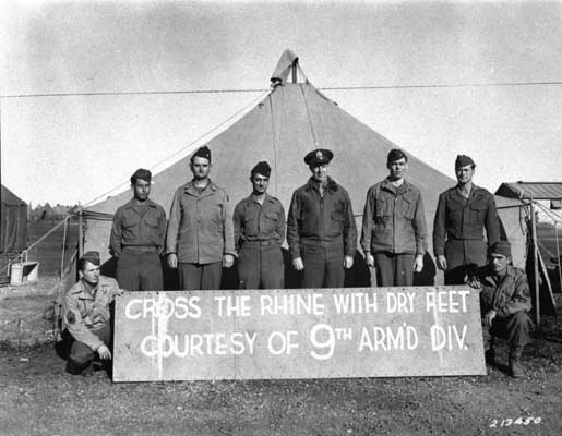 The commanding general of the 9th Armored Division (third from right), and members of the division who won the Distinguished Service Cross pose with the sign placed on the Ludendorff Bridge after its capture. US Army Signal Corps photograph taken by  W. Spangle on September 18, 1945, several months after the bridge was captured.