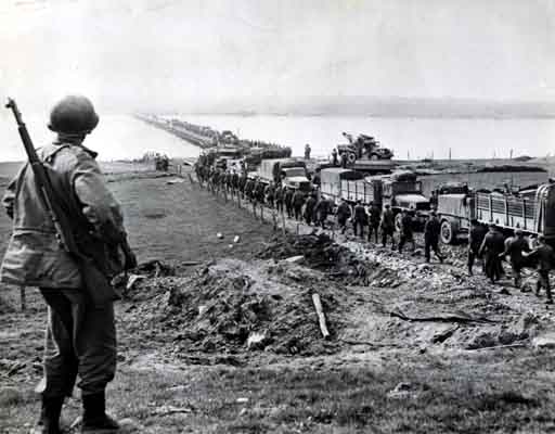 German prisoners file across the Rhine as American supply trucks move forward toward the front. March 26, 1945. US Army Signal Corps photograph.