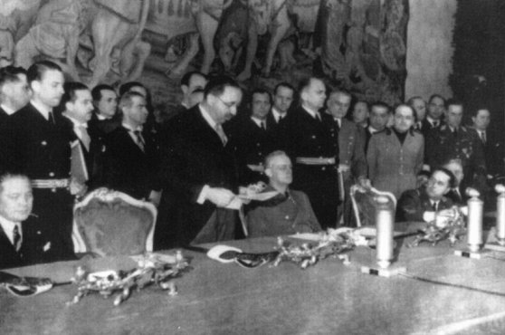 Bulgarian leader Bogdan Filov (standing) and German foreign minister Joachim von Ribbentrop (seated, center) during the signing of the Tripartite Pact. This treaty formally aligned Bulgaria with the Axis powers. Vienna, Austria, March 1, 1941.