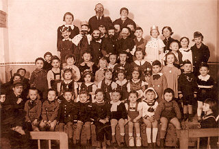Kindergarten class photograph taken during Purim. Agnes' brother is in the front row in a white sailor suit. Agnes is seated to her brother's right. 1934–1935.