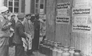 Jewish survivors in a displaced persons camp post signs calling for Great Britain to open the gates of Palestine to the Jews. Germany, after May 1945.