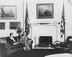 President Franklin Roosevelt sits with Eleanor Roosevelt...