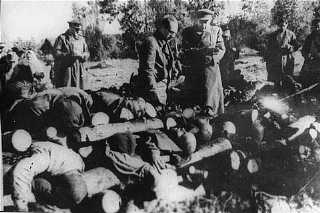 Soviet officials view stacked corpses of victims at...