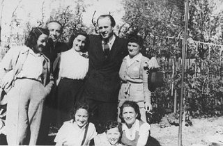 Oskar Schindler standing (second from right) with some of the people he rescued.