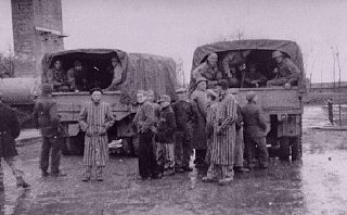 Survivors of the Buchenwald concentration camp gather around trucks carrying American troops.