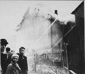 "As the synagogue in Oberramstadt burns during Kristallnacht (the ""Night of Broken Glass""), firefighters instead save a nearby house. Local residents watch as the synagogue is destroyed. Oberramstadt, Germany, November 9-10, 1938."