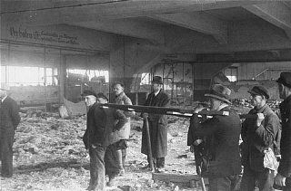 Under orders of the US First Army, German civilians prepare to use a stretcher to remove corpses of victims of the Dora-Mittelbau concentration camp, near Nordhausen. Germany, after April 10, 1945.