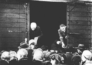 Jews being deported from the Warsaw ghetto board a...