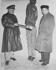During a US Army chaplain inspection of the newly liberated Buchenwald concentration camp, G. Bromley Oxnam (right), the Methodist bishop of New York and President of the Federated Council of Churches of Christ in America, views a demonstration of how prisoners were tortured in Buchenwald. Buchenwald, Germany, April 27, 1945.