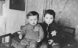 Two young brothers, seated for a family photograph...