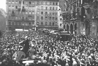 A large crowd gathers in front of the Rathaus to hear...