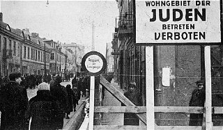 "A German postcard showing the entrance to the Lodz ghetto. The sign reads ""Jewish residential area—entry forbidden."" Lodz, Poland, 1940-1941."