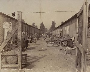 Survivors move around between rows of barracks in the...