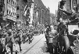 Members of the Hitler Youth march before their leader...