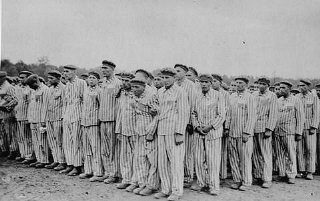 Prisoners during a roll call at the Buchenwald concentration camp. Their uniforms bear classifying triangular badges and identification numbers. Buchenwald, Germany, 1938-1941.