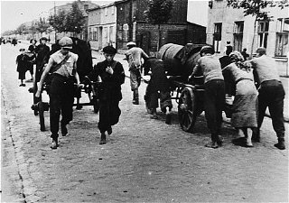 Jews at forced labor, transporting excrement down a ghetto street. Lodz ghetto, Poland, wartime.
