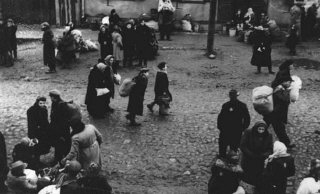 Jews carrying bundles of possessions before their deportation...
